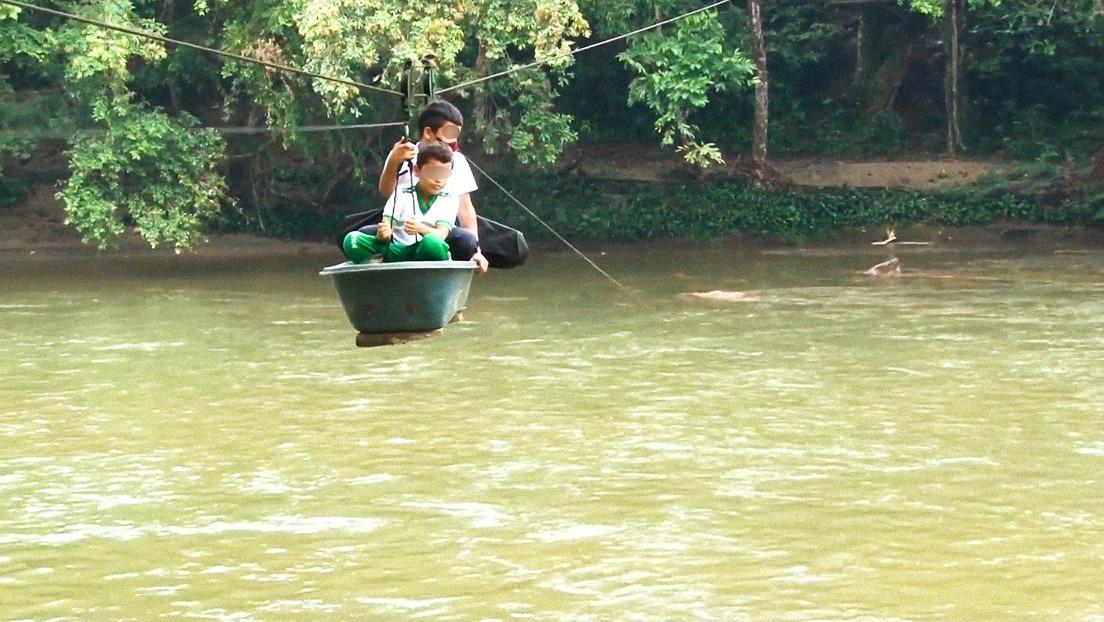 Colombia: niños arriesgan su vida cruzando un río en un teleférico casero para llegar al colegio